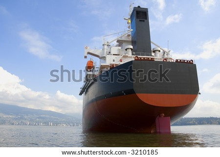 The stern and funnel of an empty freighter anchored off the west coast of North America. - stock photo