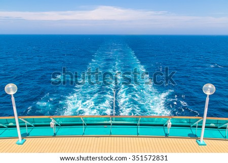 The stern of a ship with the trail in the sea in the background - stock photo