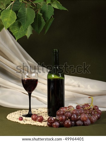 The still-life is executed from red wine and grapes - stock photo