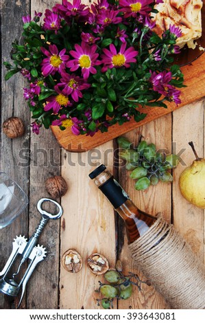 The still life with white wine in glass bottle on wood background. Glasses of wine with fresh grapes. Bottle and footed glass. Fresh ripe white grapes, walnuts, juicy ripe pear. Drink. Rustic style.