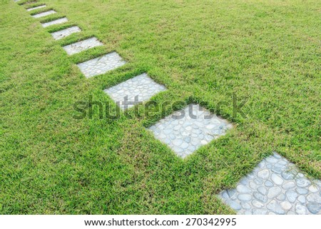 The stone block walk path in the garden with green grass - stock photo