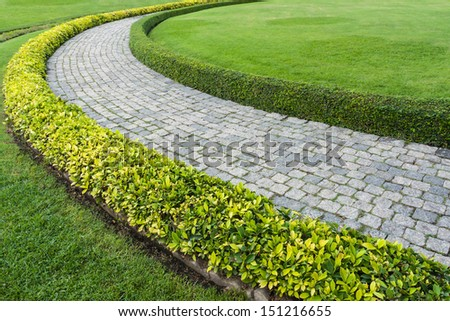 The Stone block walk path in the park with green grass background - stock photo
