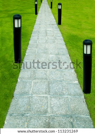 The Stone block walk path with garden lamp on green grass background - stock photo