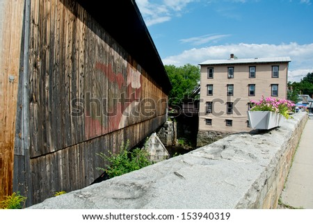 The stone bridge and the wooden covered bridge connect the two sides of town in Contoocook, New Hampshire. - stock photo