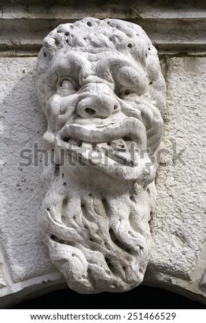 The stone mask on a bridge in Venice, Italy, Venice lagoon - UNESCO World Heritage Site - stock photo