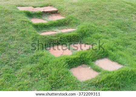 The stone path through on green grass in the garden. - stock photo