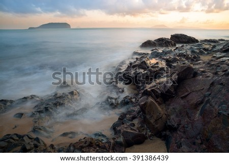 The stones at the beach and calm sea water with sunrise moments at background.