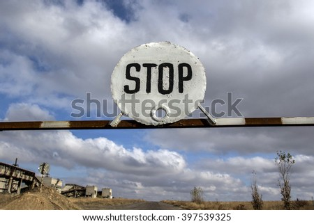 the stop sign on the barrier on the background of blue sky with clouds