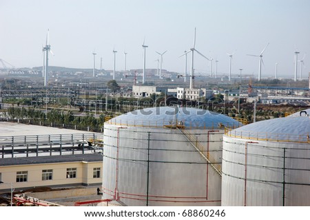The storage tanks at an oil refinery complex/Oil Tanks and wind power - stock photo