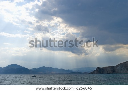 The storm sky above the sea with a lonely yacht - stock photo