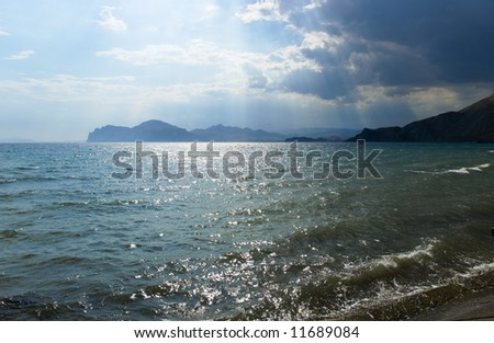 The storm sky above the sea with mountains on a background - stock photo