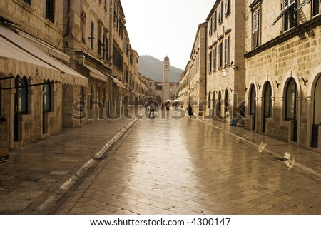 The Stradun (sometimes the Strada) is the main shopping street and gathering area in the city of Dubrovnik in Croatia. The cobblestones have been polished smooth over hundreds of years. - stock photo