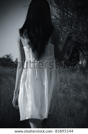The strange mysterious girl in white dress with shoes in hand is on the field. Rear view, black and white photo - stock photo