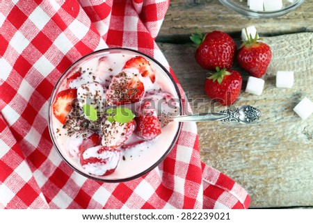 The strawberry in the yogurt. Bowl with cream and strawberries. Sugar cubes, berries and a delicious dessert. Checkered tablecloth on the table. A restaurant, a coffee shop, ordering food. Sweet food. - stock photo