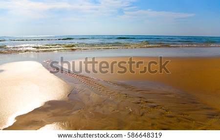 The stream flows through the yellow sand in the ocean.
