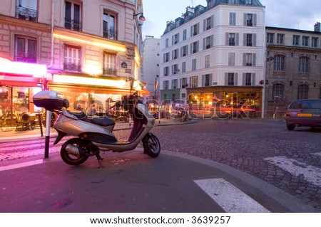 The streets of Paris are still full of activity, lit by neon advertisements, signs and billboards; people lingering on the terraces and cars rushing by. Nightlife in Montmartre - stock photo
