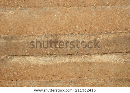 The striations, natural earthtone colors, and textures of a rammed earth wall, the latest ecological building material.  - stock photo