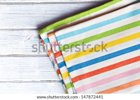 the striped kitchen napkin on wooden table - stock photo
