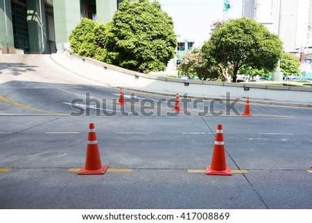 The Striped orange cones and car fragment on the asphalt road - stock photo