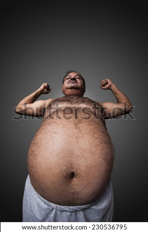 The strong and fat man showing his muscles and belly. - stock photo