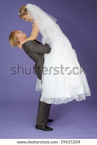 The strong groom holds the admired bride on hands - stock photo