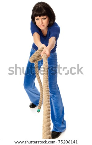 The strong-willed woman plays of pulling of a rope and wins - stock photo
