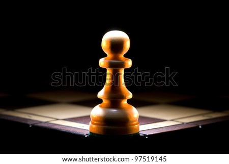 The struck pawn on a chess board. A dark art background. - stock photo
