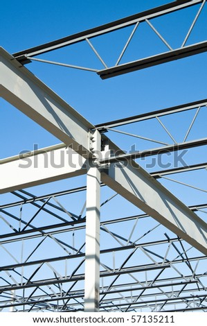 the structural steel structure of a new commercial building against a clear blue sky in the background