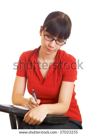 The student in glasses writes something - stock photo