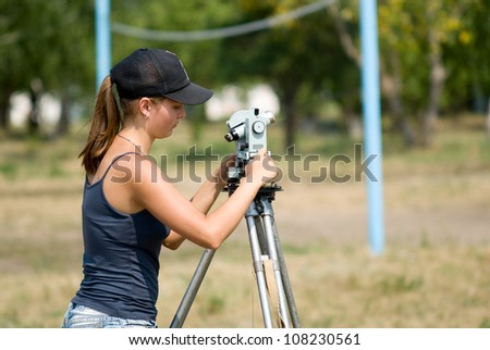 The student learns to work with a theodolite at practice - stock photo