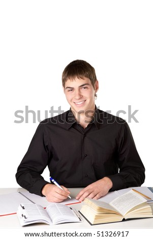 The student sits at a table with books and smiles
