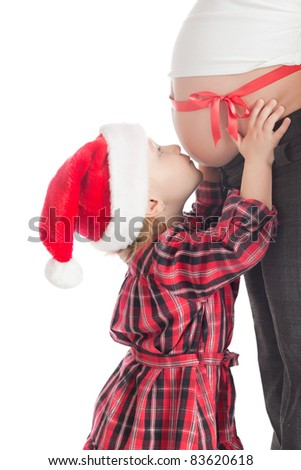 the studio shot of little girl kissing christmas gift - pregnant mother - stock photo