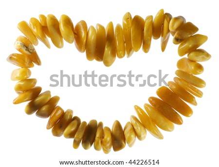 The stylised heart from yellow amber stones. A gift at date of sacred Valentine. Isolated on white.