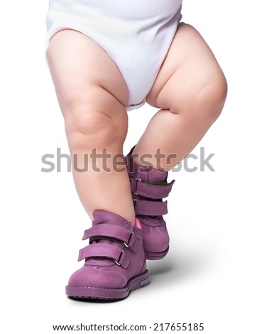 the stylish baby goes in boots. it is isolated on a white background - stock photo