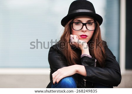 the stylish sad city girl in sunglasses leans a cheek on a hand - stock photo