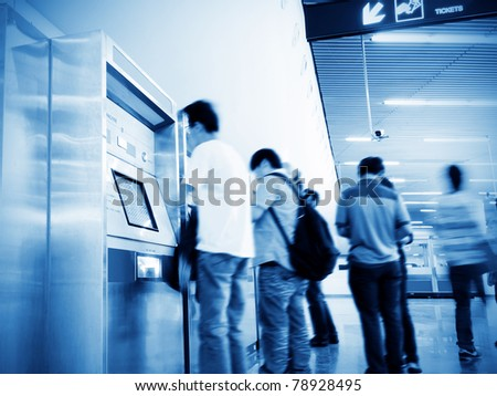 The subway, ticket machine, a group of people are waiting.