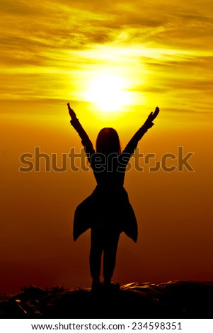 The success concept of silhouette of Young woman standing arms made  Under the Rising Sun