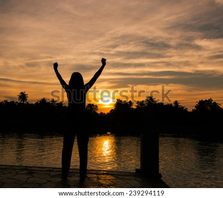 The success concept of silhouette of Young woman standing arms made Under the Rising Sun - stock photo