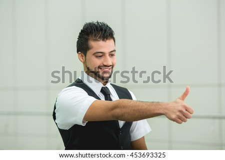 The success indian businessman show thumb up and look