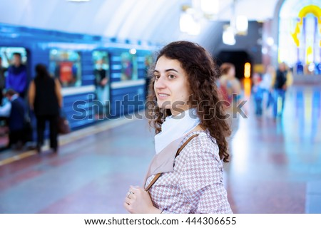The successful business woman in the subway waiting for the train. The train and peoples on blurred background. - stock photo