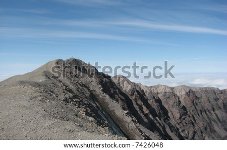 The summit of Mt. St. Helens post-eruption with hikers standing on the true summit. - stock photo
