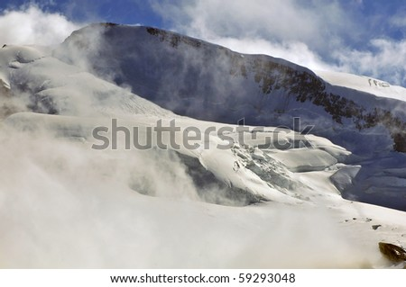 the summit ridge of the Strahlhorn partially  hidden in the clouds in the southern swiss alps - stock photo