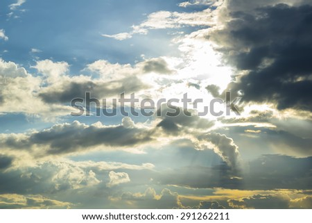 The sun breaking through dramatic clouds - stock photo