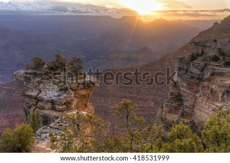 The sun breaks through the clouds in the East over the canyon seen from Mather Point in Grand Canyon National Park, Arizona. - stock photo