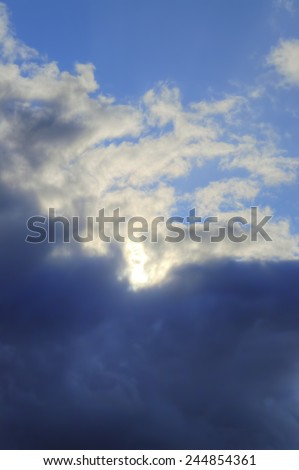The Sun Disappears Behind Dark Clouds - stock photo
