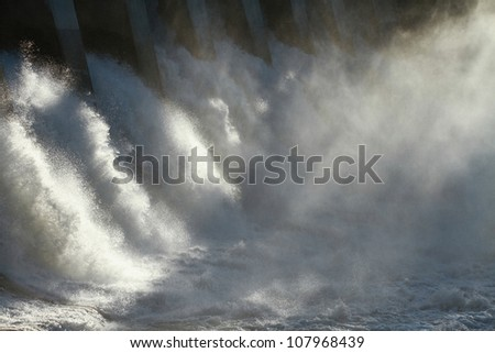 The sun dramatically backlighting the spillway and spray of a large hydroelectric dam overflow. - stock photo