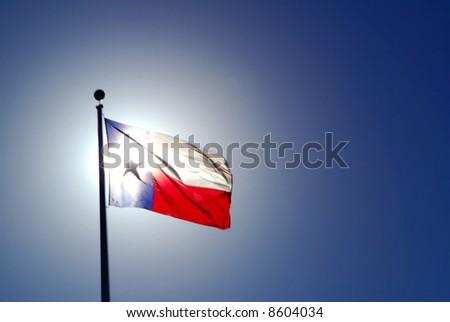 The sun is backlighting the Texas flag. - stock photo