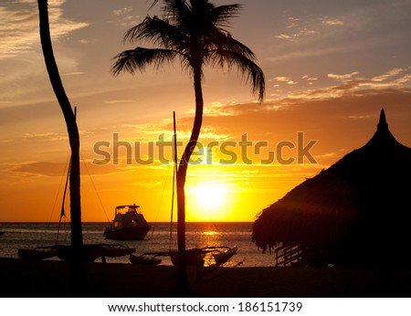 The sun is setting across the ocean waters of Palm Beach in the town of Noord.