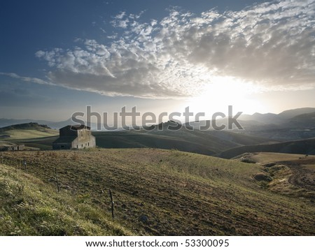 the sun is setting on the countryside with abandoned farmhouse in the sicilian hinterland - stock photo