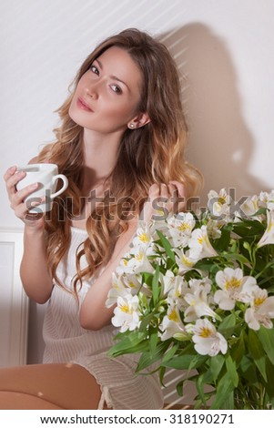 The sun is shining into the bedroom, she looks out the window. The lady sitting beside the bed, her hand near her head, she looks into the camera. Morning coffee, enjoyment, she closed her eyes - stock photo